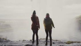 Задний взгляд 2 счастливых женских туристов около водопада Gljufrabui в Исландии Скакать женщин визирования утехи близко сток-видео