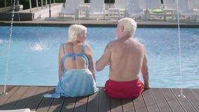 Задний взгляд счастливых зрелых пар сидя на краю бассейна Милый старший человек и женщина ослабляя в гостинице видеоматериал