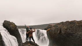 Задний взгляд счастливых пар после пешего туризма Путешествующ человек и женщина стойте около водопада в Исландии и поднимать рук видеоматериал