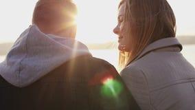 Задний взгляд счастливых пар сидя на выравниваясь озере на заходе солнца сток-видео