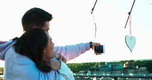 Задний взгляд счастливых эмоциональных любящих пар обнимая и принимая selfies на крыше украшенной с сердцами романтично сток-видео