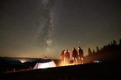 Друзья отдыхая около лагеря, лагерного костера под небом ночи звездным стоковые фото