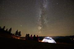Друзья отдыхая около лагеря, лагерного костера под небом ночи звездным стоковые изображения