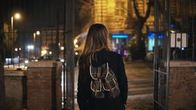 Задний взгляд туристской женщины с рюкзаком идя через темный парк около дороги поздно на ночу самостоятельно Стоковая Фотография RF