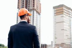 Задний взгляд успешного менеджера смотря строительную площадку Стоковые Фото