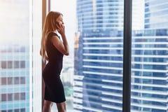 Задний взгляд успешной коммерсантки имея телефонный разговор смотря вне окно с взглядом городского пейзажа Стоковые Изображения