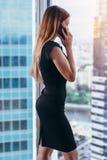 Задний взгляд успешной коммерсантки имея телефонный разговор смотря вне окно с взглядом городского пейзажа Стоковое Фото