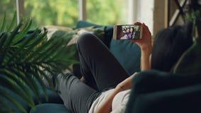 Задний взгляд черно-с волосами дамы лежа на софе дома и звоня видео- связывая с парами друзей милыми акции видеоматериалы