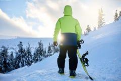 Задний взгляд snowboarder взбираясь с его доской на держателе для backcountry встречи freeride в лесе на заходе солнца стоковые изображения rf
