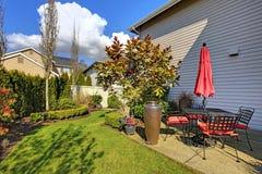 Задний двор дома весны с красными стулами Стоковая Фотография RF