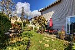 Задний двор дома весны с красными стулами Стоковые Фото