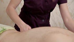 Задний массаж Массажи Masseur более низкая задняя часть мужского спортсмена Masseur девушки в пурпурном костюме делает терапевтич акции видеоматериалы