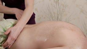Задний массаж Массажи Masseur более низкая задняя часть мужского спортсмена Masseur девушки в пурпурном костюме делает терапевтич сток-видео