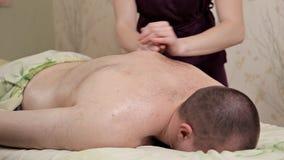 Задний массаж Masseur девушки в пурпурном костюме делает расслабляющий массаж сток-видео