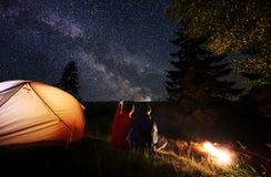 Задний мужчина взгляда показывает женщину вверх на выравнивать звёздное небо на млечном пути около шатра и костра на горах предпо Стоковое Изображение RF