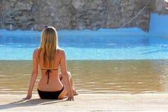 Задний портрет взгляда незамужней женщины наблюдая на водном бассейне стоковое изображение