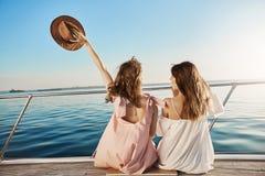 Задний портрет 2 женских друзей сидя на шлюпке, развевающ с шляпой пока говорящ и наслаждающся смотрящ взморье Стоковая Фотография