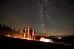Друзья отдыхая около лагеря, лагерного костера под небом ночи звездным стоковые фотографии rf