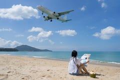 Задняя сторона женщины сидя на пляже и посмотренной карте, Backgrou Стоковые Фотографии RF