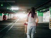 Задняя сторона от женщины с движением магазинной тележкаи и ищет ее ca Стоковое Изображение