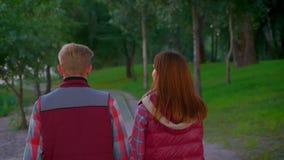 Задняя стрельба на просыпать пара которая любит один другого и руки владением нежно, прогулка в зеленом свежем парке, указывая же видеоматериал