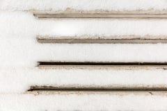 Задняя часть белой деревянной скамьи покрытой с снегом Стоковое Изображение