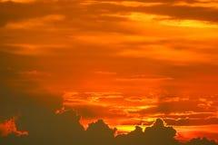задняя часть захода солнца на последнем светлом красном оранжевом облаке силуэта неба стоковое изображение rf