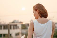 Задняя часть положения женщины на заходе солнца стоковое изображение rf