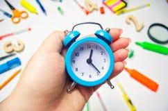 задняя школа к голубой будильник на столе школы в руках студента stationery воцарения Белая предпосылка стикеры стоковые фотографии rf