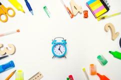 задняя школа к голубой будильник на столе школы stationery воцарения Белая предпосылка стикеры, покрашенные ручки, карандаши, s стоковое изображение
