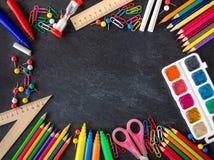 задняя школа предпосылки к Школьные принадлежности на черной доске мела Стоковая Фотография