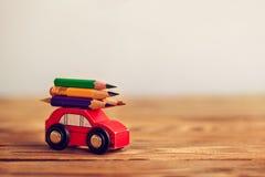 задняя школа принципиальной схемы к Миниатюрный красный носить автомобиля красочные карандаши на деревянном столе стоковое изображение