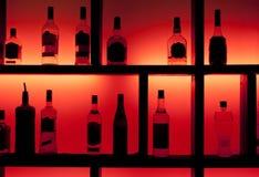 задняя штанга разливает освещенный коктеил по бутылкам Стоковые Изображения