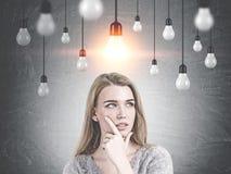 Задумчивая белокурая женщина daydreaming, идея электрической лампочки стоковые изображения rf