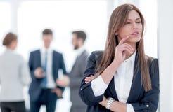 Задумчивая бизнес-леди на запачканной предпосылке офиса стоковые изображения
