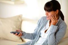 Задумчивая девушка сидя на софе используя remote tv Стоковое Изображение RF