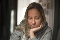 Задумчивая женщина дома, сидящ на стуле стоковые фотографии rf