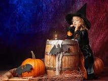 Задумчивая маленькая девочка в костюме ведьмы сидя на тыкве в a Стоковая Фотография