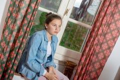 Задумчивая молодая девушка подростка около окна стоковое фото