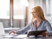 Задумчивая молодая женщина используя современный компьютер для работы стоковые фотографии rf