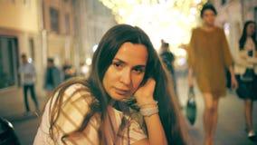 Задумчивая молодая женщина на загоренной пешеходной предпосылке улицы видеоматериал