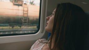 Задумчивая молодая женщина смотря из окна поезда Перемещение, концепция перехода сток-видео