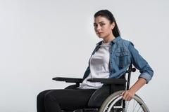 Задумчивая поврежденная кресло-коляска женщины касающая Стоковые Изображения