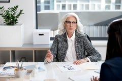 Задумчивая постаретая дама трудится с документами Стоковые Изображения
