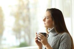 Задумчивая серьезная женщина смотря через окно Стоковое Фото