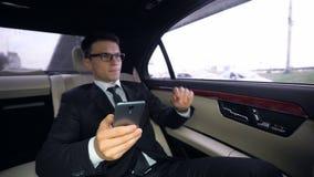 Задумчивая электронная почта сочинительства бизнесмена, ехать в автомобиле, напряженная работа, трудоголик акции видеоматериалы