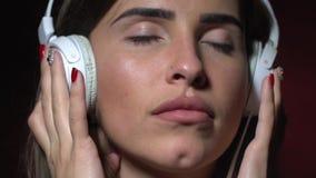 Задумчивое брюнет с прошивкой в носе слушая к музыке на наушниках акции видеоматериалы