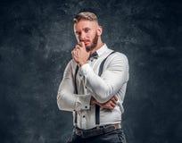 Задумчивое мужское думающ около что-то важное Стильно одетый молодой человек в рубашке с представлять бабочки и подтяжок стоковая фотография