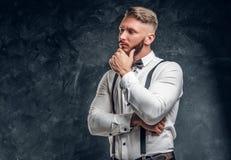 Задумчивое мужское думающ около что-то важное Стильно одетый молодой человек в рубашке с представлять бабочки и подтяжок стоковая фотография rf