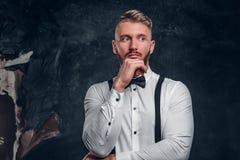 Задумчивое мужское думающ около что-то важное Стильно одетый молодой человек в рубашке с представлять бабочки и подтяжок стоковое фото rf